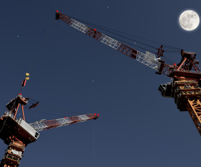 Low angle view of full moon rising over the Crane with copy space.