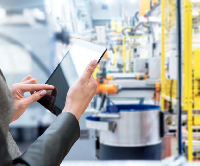 Horizontal color image of businesswoman - unrecognizable person - working with digital tablet in large futuristic factory. Focus on businesswoman's hands holding black tablet, futuristic machines in background.