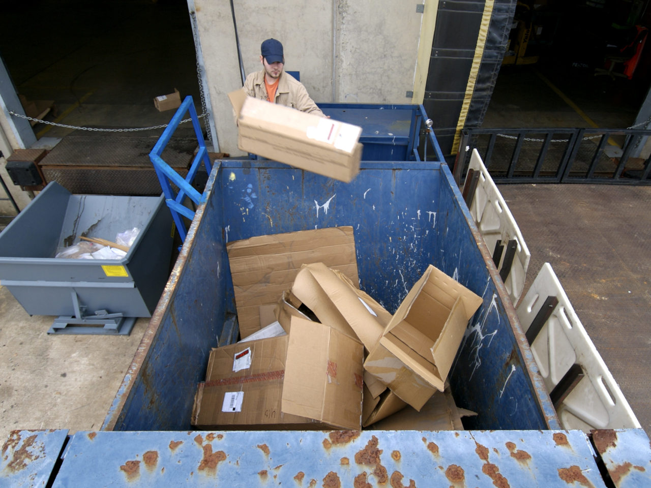 Worker throws empty cardboard boxes into an industrial trash compactor, part of the process for recycling the boxes.