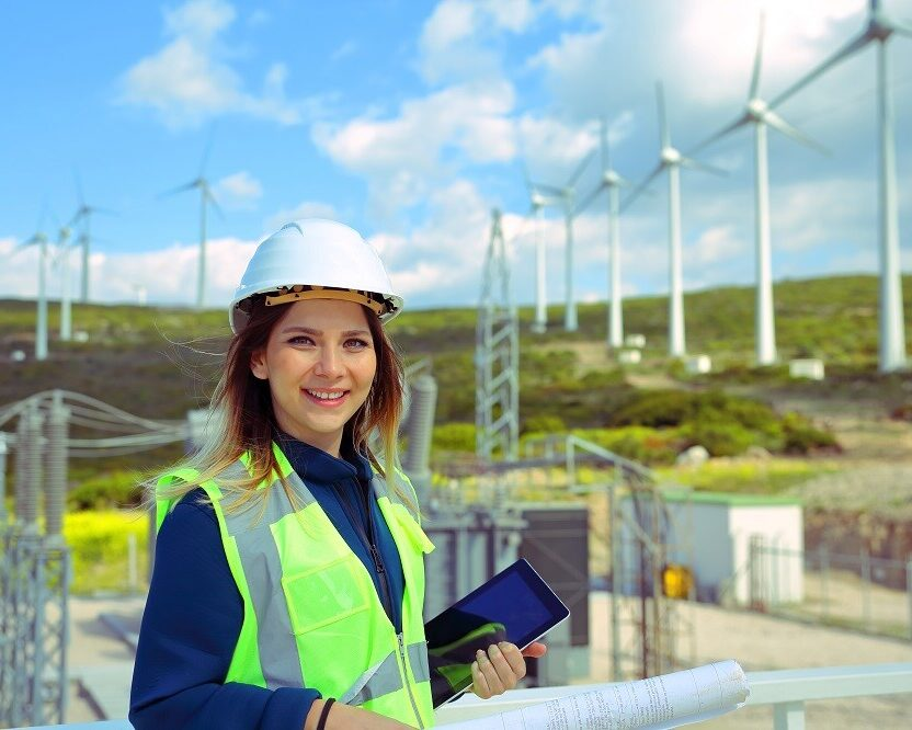 Female engineer holding blueprints and checking wind turbines