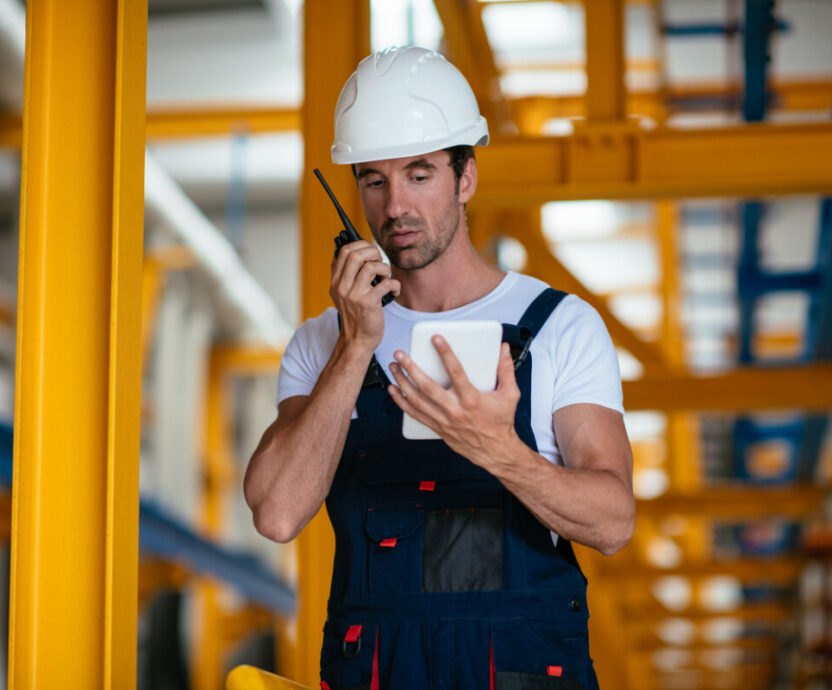 Engineer in factory with walkie talkie. Shallow DOF. Developed from RAW; retouched with special care and attention; Small amount of grain added for best final impression. 16 bit Adobe RGB color profile.