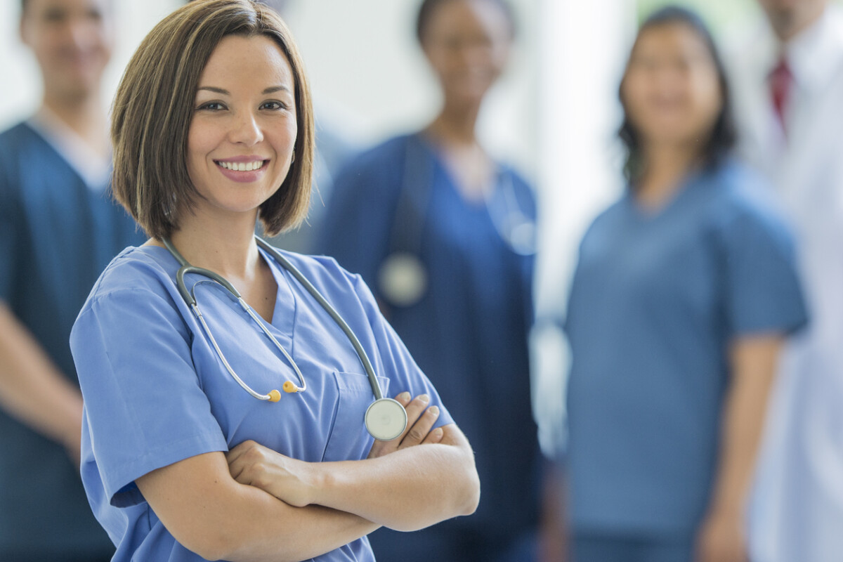 A multi-ethnic group of medical professionals are standing together in a medical office. A female medical professional stands in front of the group with arms crossed.