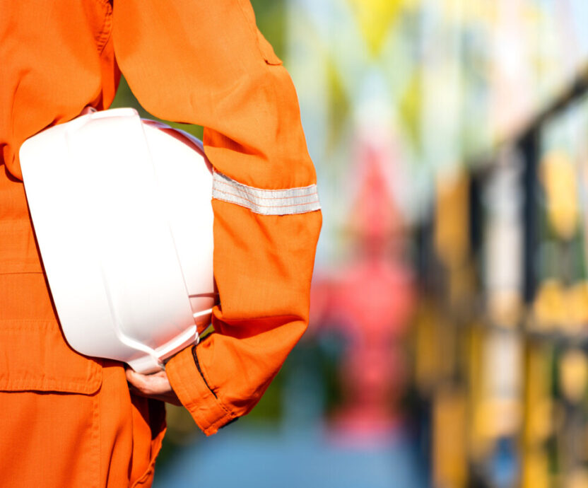 Oil field operator or worker is holding white safety hardhat, prepare to start the job on working platform (as background). Safety in operation concept photo.