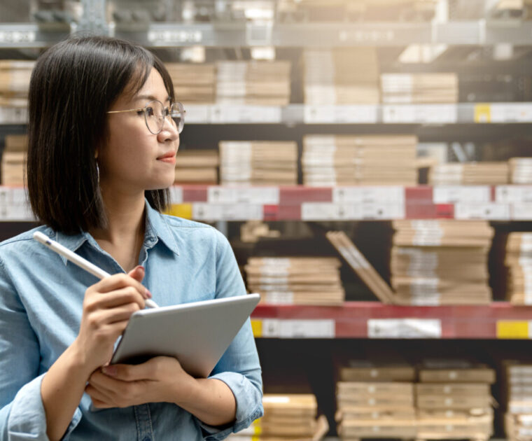 Young attractive asian worker, owner, manager, entrepreneur woman holding smart tablet computer with efulfillment service business warehouse management stock online concept. Asian sme merchandise.