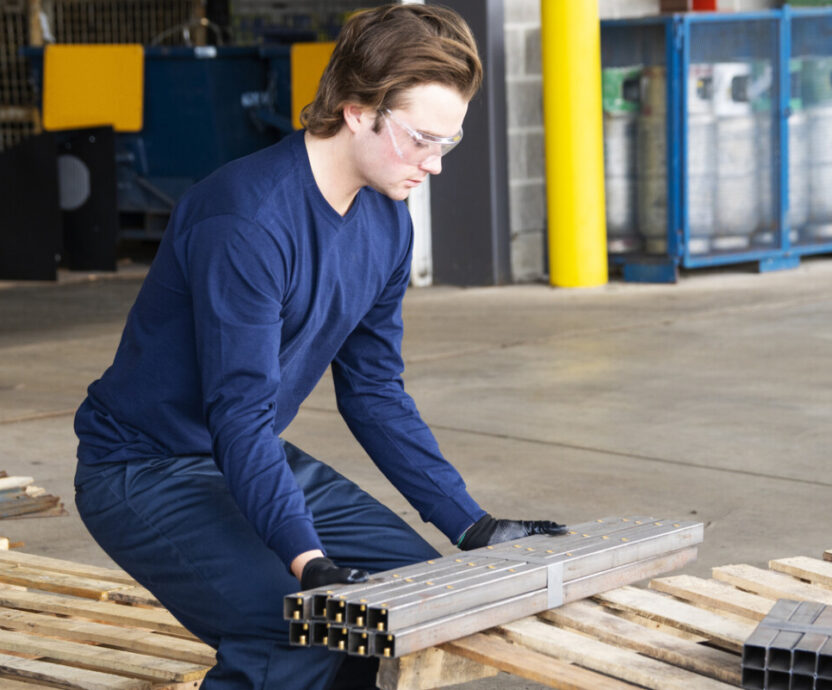 An industrial safety topic. A young male factory worker using a proper lifting technique