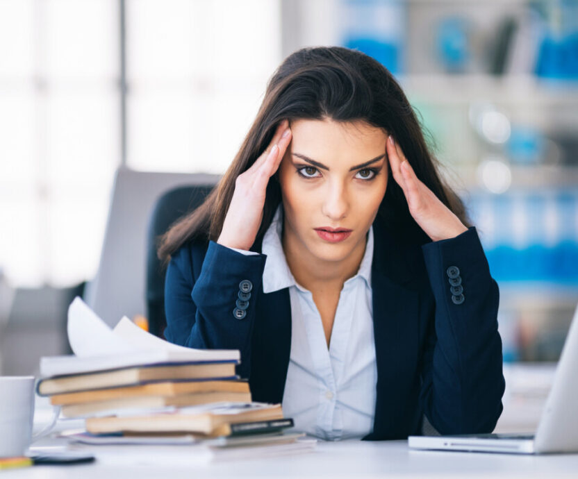 Stressed businesswoman suffering from headache at office
