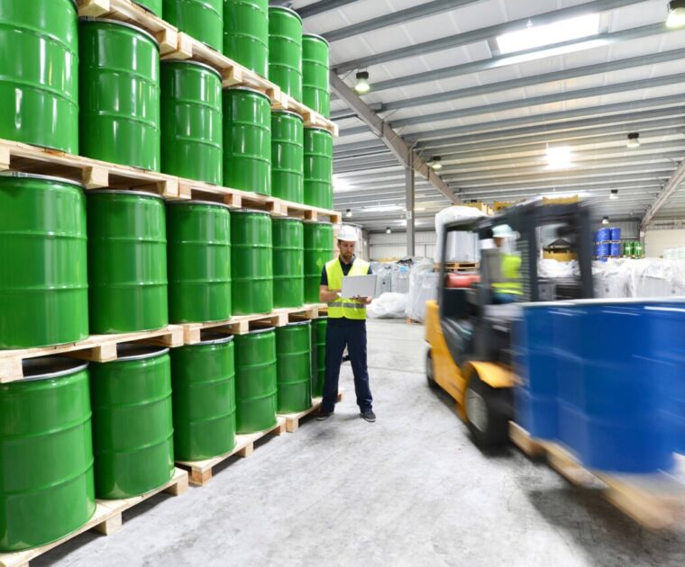 Worker in a warehouse completing a safety audit on a device